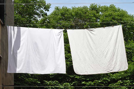 drying: Clothes line with two white bed sheets Stock Photo