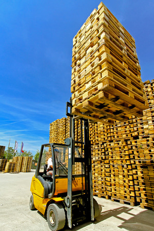 Forklift operator lifting bunch of euro pallets photo