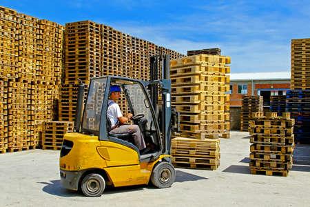 pallet: Forklift operator handling wooden pallets in warehouse