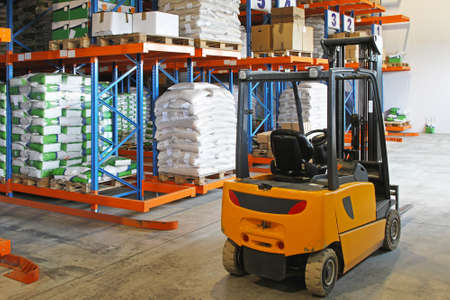 Forklift truck in distribution warehouse with racks photo