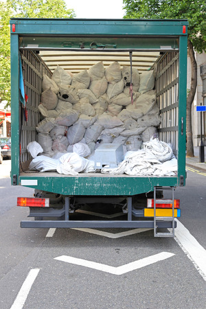 delivers: Big delivery truck collecting dirty laundry bags