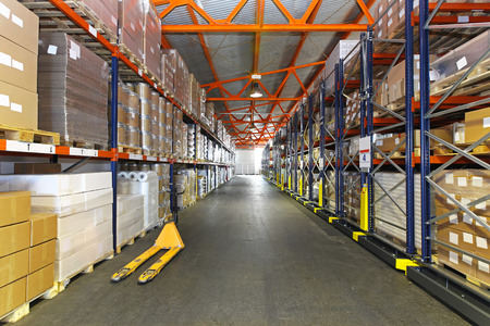 Long corridor with shelving system in distribution warehouse photo