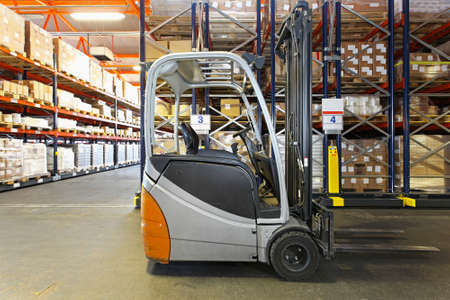shelving: Electric forklift in distribution warehouse Stock Photo
