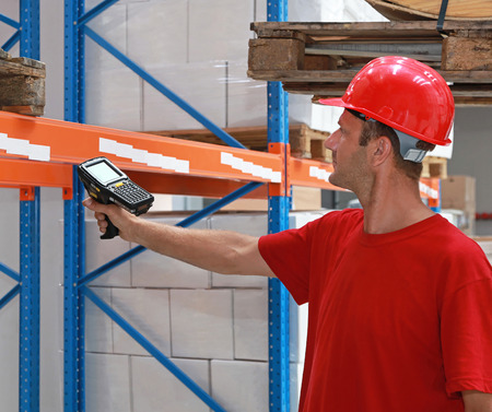Worker in distribution warehouse with handheld barcode scanner photo