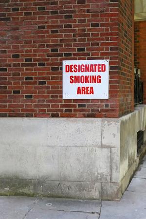 designated: Designated smoking area sign at building corner