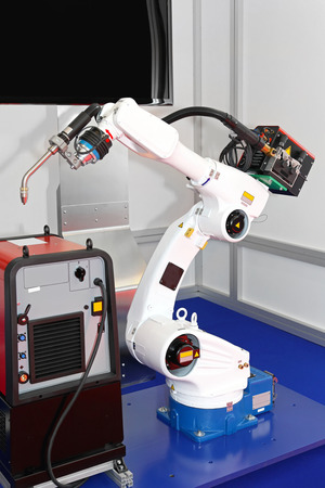 mechanized: White robotic arm for welding in factory