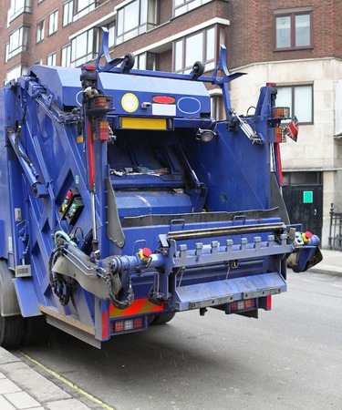 dump truck: Back of a big blue garbage truck in city