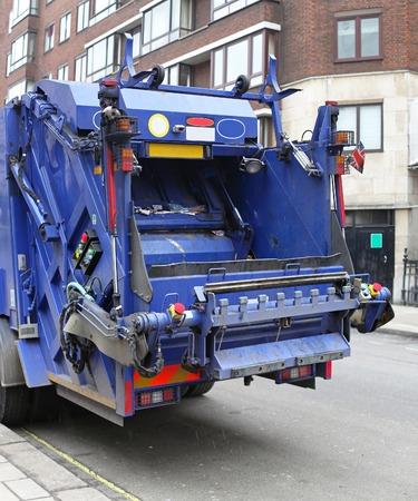 Detrás de un gran camión de basura azul en la ciudad Foto de archivo