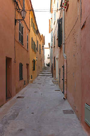 Narrow street and traditional houses in Saint Tropez photo
