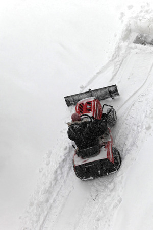Small tractor with snowplow removing heavy snow photo