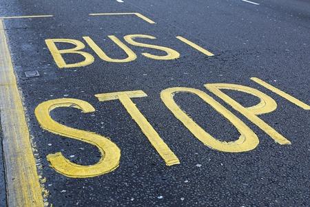 bus stop: Yellow bus stop sign at asphalt