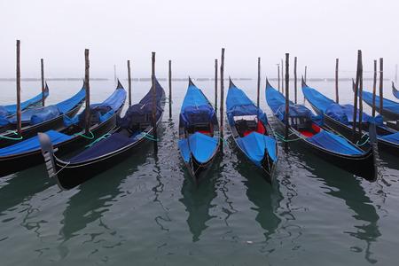 gondola: Gondola boats moored at fog in Venice canal