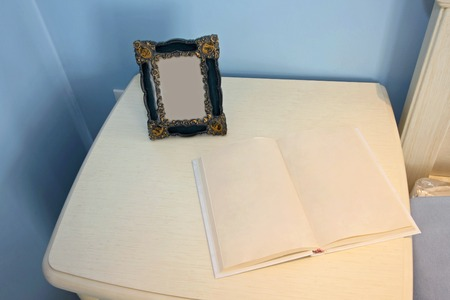 Open book and picture frame at bedside night table photo