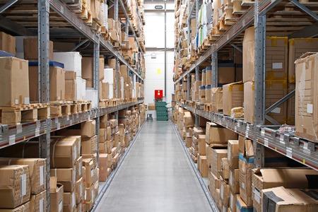 Righe di magazzino con scatole di cartone e prodotti in scaffali