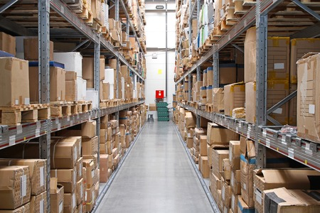 Warehouse rows with cardboard boxes and goods at shelves