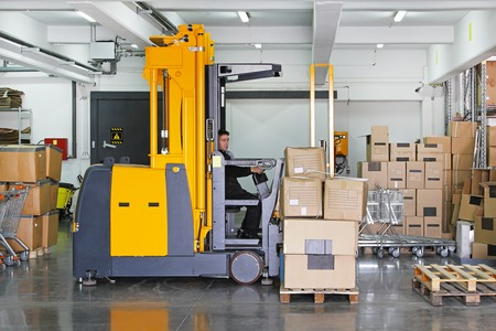 Electric forklift stacker in warehouse with boxes photo