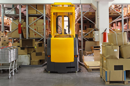 High rack stacker forklift truck in distribution warehouse photo