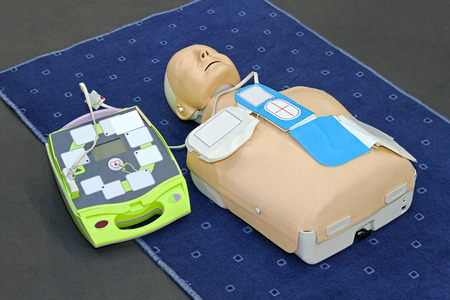 training device: Automated External Defibrillator with training dummy mannequin Stock Photo