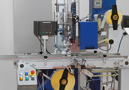 Labeling machine with conveyor belt in factory photo