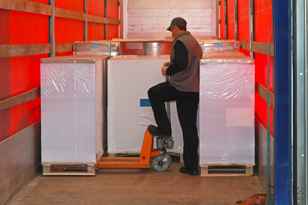 Loading goods in lorry truck with pallet jack photo