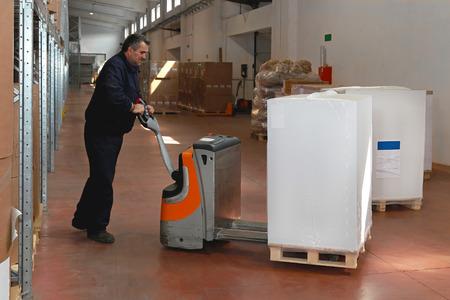 maneuvering: Maneuvering goods in warehouse with pallet jack