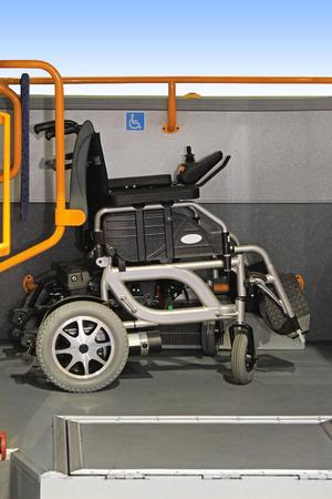 motorizado: Silla de ruedas eléctrica en el espacio asignado en el autobús público Foto de archivo