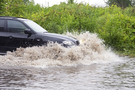 FLOODING: SUV vehicle driving fast through flood water Stock Photo