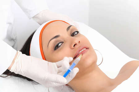 injections: Young woman having lip augmentation at beauty clinic Stock Photo