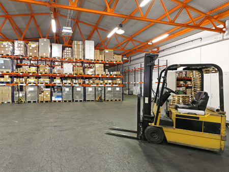 Forklift in front of shelving system at warehouse photo