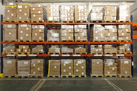 wholesale: Boxes with goods at shelves in warehouse