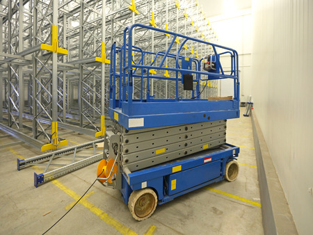 storage warehouse: Scissor lift aerial work platform in warehouse Stock Photo
