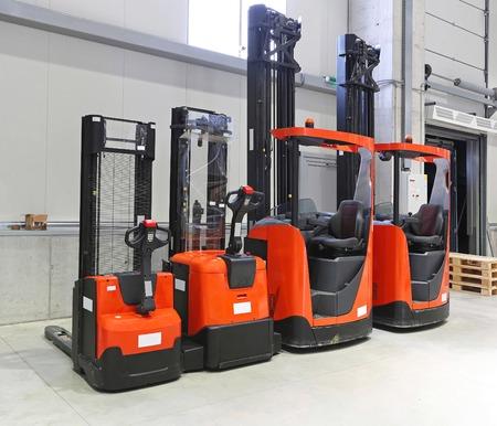 Quattro carrelli elevatori rossi in magazzino di distribuzione