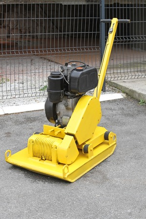 compactor: Yellow vibratory plate compactor at construction site
