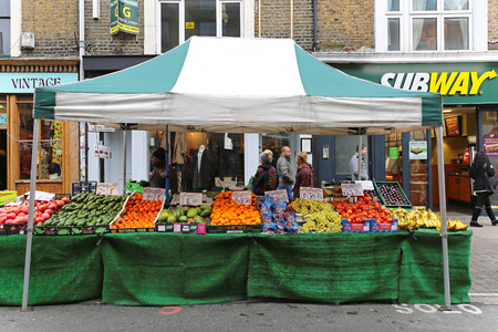 LONDON, UNITED KINGDOM - NOVEMBER 24: Brick Lane Market in East London on NOVEMBER 24, 2013. Temporary street market stall with fruits and vegetables at sunday in London, United Kingdom.