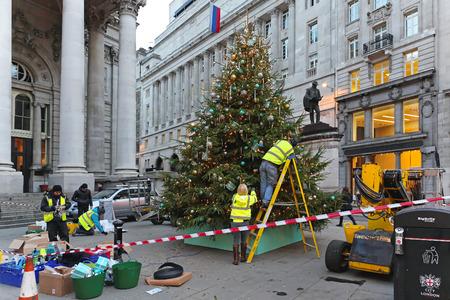 erected: LONDON, UNITED KINGDOM - NOVEMBER 23: Decorating Christmas tree in London on NOVEMBER 23, 2013. Workers erected big Christmas tree in front of Royal Exchange in London, United Kingdom.
