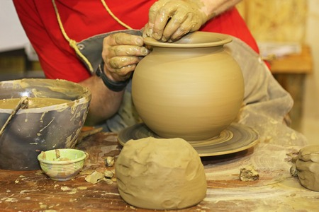 rotate: Potter making pot from clay at rotating table Stock Photo