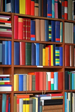 edu: Colorful books at bookshelf in library Stock Photo
