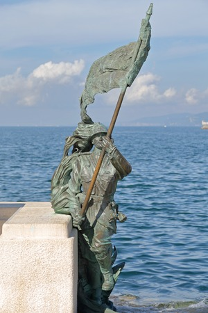 solders: TRIESTE, ITALY - OCTOBER 14: Le Bronze soldier statue with flag in Trieste on OCTOBER 14, 2014. Le Bronze sculpture, one of the symbols of the city, representing solders on the waterfront in Trieste, Italy.