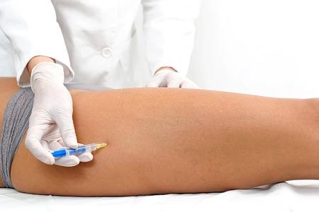 de rodillas: Mujer que tiene tratamiento de la pierna botox en clínica de belleza