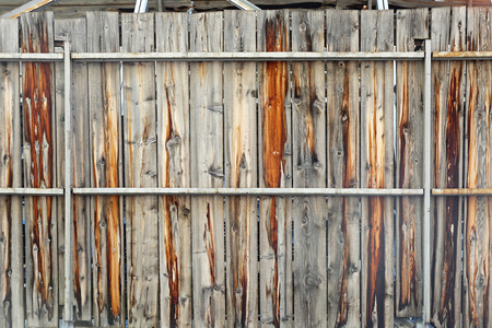 decayed: Decayed wooden fence with metal structure