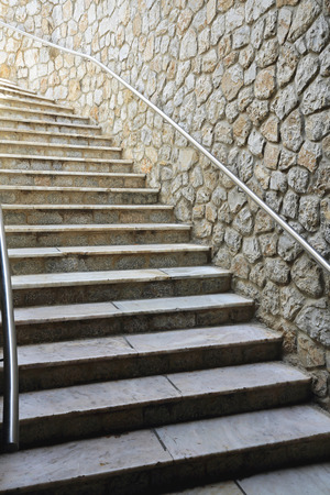 banister: Flight of Stairs with banister at stone wall Stock Photo