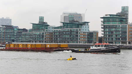 towed: LONDON, UNITED KINGDOM - JANUARY 25  Barges towed by a tugboat on the River Thames in London on JANUARY 25, 2013  Transporting waste by water in sealed containers on barges which are pulled by tug in London, United Kingdom