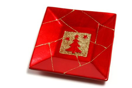 celeb: Christmas ornamental red plate with a tree isolated over a white background.