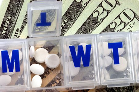 counterfeit: Close up of an open medicine container over a stack of bills.