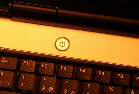 Laptop power button with a warm light. photo