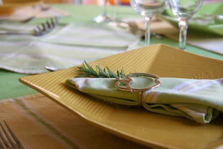 dinnerware: Yellow plate in a table with dinnerware.