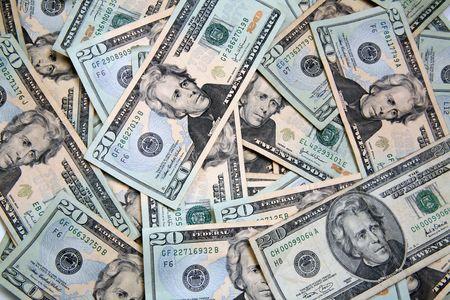 disperse: Lots of cash, twenty dollar bills, disperse over a table top, lots of money.