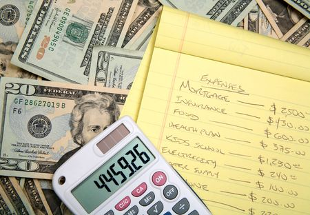 disperse: Lots of cash, twenty dollar bills, disperse over a table top with a calculator and a budget for planning.