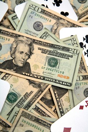 disperse: Lots of cash, twenty dollar bills, disperse over a table top and playing cards for the idea of gambling money.