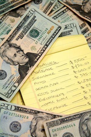 disperse: Lots of cash, twenty dollar bills, disperse over a table top drowning a budget list.